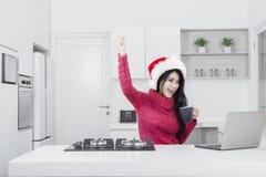 有膝上型计算机和圣诞老人帽子的成功的俏丽的女孩 免版税库存照片