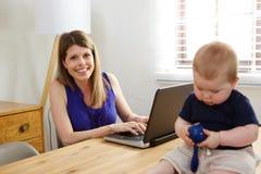 有膝上型计算机和小儿子的微笑的妇女坐桌 免版税库存图片