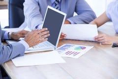 有膝上型计算机和数字式片剂的同事在会议 库存照片