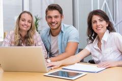 有膝上型计算机和数字式片剂的微笑的同事在会议 库存图片