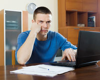 有膝上型计算机和文件的不快乐的人 免版税库存照片