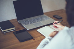 有膝上型计算机和日志的女实业家在办公室概念自由职业者的工作在家 免版税库存图片