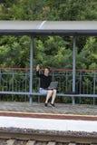 有膝上型计算机和智能手机的妇女在火车站的长凳 库存图片