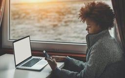 有膝上型计算机和智能手机的黑人女孩在船客舱 图库摄影