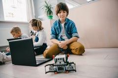 有膝上型计算机和机器人的青少年的男小学生坐地板 免版税库存照片