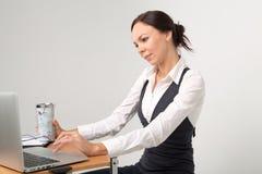 有膝上型计算机和杯子的深色的企业夫人 库存照片