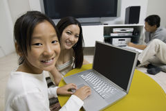 有膝上型计算机和父亲的女孩由家庭影院系统 免版税库存照片