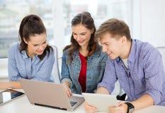 有膝上型计算机和片剂个人计算机的三名微笑的学生 免版税库存照片