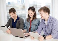 有膝上型计算机和片剂个人计算机的三名微笑的学生 免版税图库摄影