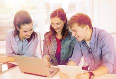 有膝上型计算机和片剂个人计算机的三名微笑的学生 库存照片