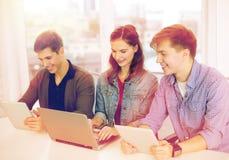 有膝上型计算机和片剂个人计算机的三名微笑的学生 免版税库存图片