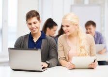 有膝上型计算机和片剂个人计算机的两名微笑的学生 库存照片