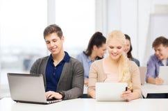 有膝上型计算机和片剂个人计算机的两名微笑的学生 库存图片