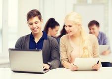 有膝上型计算机和片剂个人计算机的两名微笑的学生 免版税库存照片