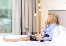 有膝上型计算机和电话的女实业家在旅馆客房 库存照片