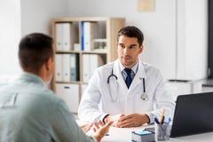有膝上型计算机和男性患者的医生医院的 免版税库存照片
