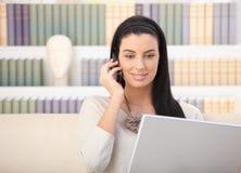 有膝上型计算机和移动电话的微笑的妇女 免版税库存图片