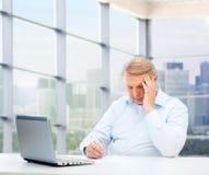 有膝上型计算机和笔文字的老人在办公室 免版税图库摄影
