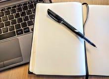 有膝上型计算机和笔的笔记本 库存图片