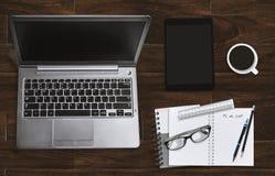 有膝上型计算机和笔记本的办公室工作场所有镜片和片剂的 顶视图 免版税库存照片