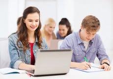 有膝上型计算机和笔记本的学生在学校 免版税库存图片