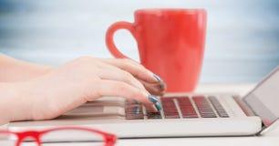 有膝上型计算机和红色咖啡杯的手反对模糊的蓝色木盘区 库存图片