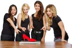 有膝上型计算机和红色鞋子的四个女孩 库存图片