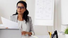 有膝上型计算机和纸的女实业家在办公室 股票录像