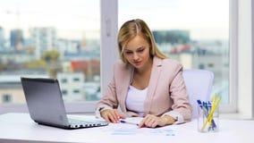 有膝上型计算机和纸的微笑的女实业家 股票录像