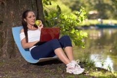 有膝上型计算机和苹果的年轻人孕妇在公园坐 免版税库存图片
