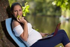 有膝上型计算机和苹果的年轻人孕妇在公园坐 免版税图库摄影