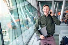 有膝上型计算机和衬衣的一个美丽的愉快的人谈话在电话和微笑在窗口后的在机场 免版税库存照片