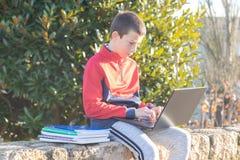 有膝上型计算机和课本的严肃的少年男孩做家庭作业和为检查做准备在公园 库存照片