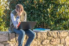 有膝上型计算机和课本的生气十几岁的男孩 不要在公园做家庭作业并且不要为检查做准备 免版税库存照片