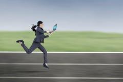 有膝上型计算机奔跑的女性企业家在轨道 免版税库存图片