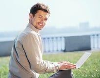 有膝上型计算机室外portrtait的年轻人 免版税库存照片