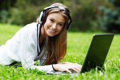 有膝上型计算机户外听的音乐的一个微笑的女孩由hea 免版税库存图片
