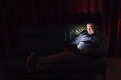 有膝上型计算机手表电影的年轻人在长沙发在家 库存照片