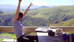 有膝上型计算机欣喜成功的女孩自由职业者,与山在背景中 股票视频
