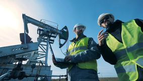 有膝上型计算机步行近的运作的井架的人 矿物燃料,石油工业概念 股票录像