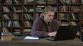 有膝上型计算机电子教学的英俊的学生在家 影视素材