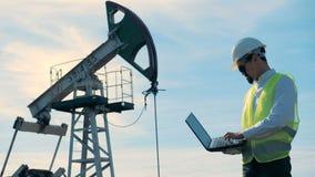 有膝上型计算机的一个人在油田工作在油泵附近 股票视频