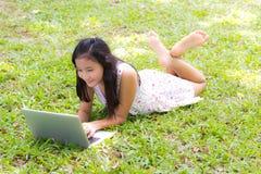 有膝上型计算机的一个女孩 免版税库存照片