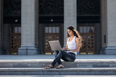 有膝上型计算机的一个少妇坐台阶,在univ附近 免版税库存图片