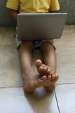 有膝上型计算机的一个男孩 免版税库存图片