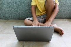 有膝上型计算机的一个男孩 免版税图库摄影