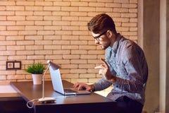 有膝上型计算机的一位人有胡子的自由职业者在晚上工作 库存照片