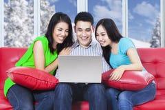 有膝上型计算机的三个亚裔少年在家 库存照片