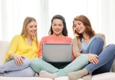 有膝上型计算机的三个微笑的十几岁的女孩在家 免版税库存图片