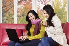 有膝上型计算机的两个亚洲人女孩在沙发 图库摄影